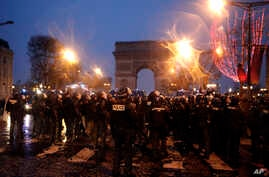 Police secure the Champs-Elysees, Dec. 15, 2018, in Paris. Demonstrations against France's high cost of living — sapped by cold weather, rain and recent concessions by French President Emmanuel Macron — were significantly smaller Saturday than at pre