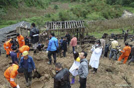 Rescuers search for victims after a landslide engulfed a building of a primary school at Zhenhe village of Yiliang county, Yunnan province, China, October 4, 2012.