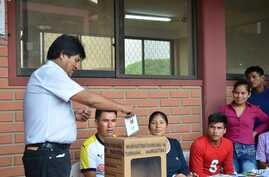 Bolivia's President Evo Morales, left, casts his ballot at a polling station in Villa 14 de Septiembre, in the Chapare region, Bolivia, Sunday, Feb. 21, 2016.