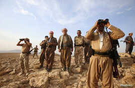 Kurdish Peshmerga forces stand guard near the town of Makhmur, south of Erbil, capital of Iraqi Kurdistan after Islamic State (IS) insurgents withdrew August 18, 2014.