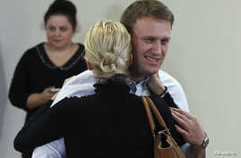 Russian opposition leader Alexei Navalny embraces his wife Yulia after the announcement of the verdict at a court building in Kirov, October 16, 2013. A Russian court on Wednesday upheld the theft conviction against Navalny but suspended his five-yea