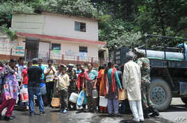 Indian residents gather to collect drinking water in buckets from an Indian Army water tanker as the city faces water shortage in Shimla, in the northern state of Himachal Pradesh on June 2, 2018.