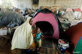 FILE - An African migrant sits with her son beside her tent at a makeshift camp set up under the bridge of a motorway on the outskirts of Algiers, Algeria, June 28, 2017.