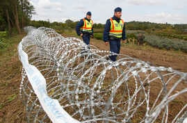 Hungarian police officers patrol an area at the temporary border fence positioned at the green border between Hungary and Croatia at Zakany, 234 km (145 miles) southwest of Budapest, Hungary, Sept. 30, 2015.