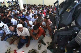 A police officer stands guard as ethnic Rohingya men gather upon arrival at a temporary shelter for migrants whose boats were washed ashore on Sumatra island on Sunday, in Lhoksukon, Aceh province, Indonesia, May 13, 2015.
