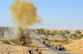 FILE - Iraqi army soldiers clear the roads from roadside bombs after defeating the Islamic State group extremists from villages outside Ramadi, west of Baghdad.
