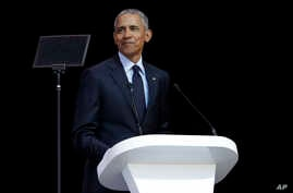 Former U.S. President Barack Obama, left, delivers his speech at the 16th Annual Nelson Mandela Lecture at the Wanderers Stadium in Johannesburg, South Africa, July 17, 2018.
