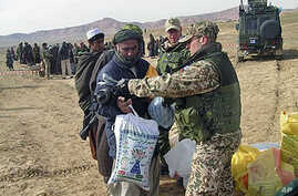 A Finnish soldier with the International Security Assistant Force gives donations to an Afghans in Chemtal district of Balkh province north of Kabul, Afghanistan on Wednesday, February 2008. (file photo)