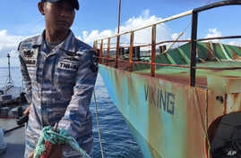 FILE - A member of the Indonesian Navy is seen anchoring a Navy ship next to illegal fishing vessel Viking which was seized by Indonesia's Navy before its sinking in the waters off Pangandaran, West Java, Indonesia, March 14, 2016.