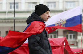 A participant wears a Russian flag during a pro-Russian rally outside the regional administration in Donetsk, March 17, 2014.