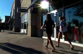 Shoppers walk by stores amid higher consumer confidence this month, which jumped to the highest level since February, at the Loop in Methuen, Massachusetts, September 24, 2012.