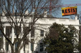 """A banner unfurled by Greenpeace demonstrators that reads """"Resist"""" is seen at the construction site of the former Washington Post building, near the White House in Washington, Jan. 25, 2017, after police say protesters climbed a crane at the site refu"""