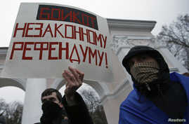 A man holds a poster during a pro-Ukrainian rally in Simferopol, March 11, 2014.