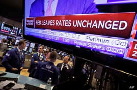 The rate decision of the U.S. Federal Reserve appears on a television screen, on the floor of the New York Stock Exchange, in New York City, Sept. 20, 2017.