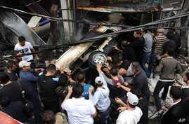 This photo released by the Syrian official news agency SANA shows Syrians pushing a car at the scene after a blast in Damascus, Syria, November 5, 2012.