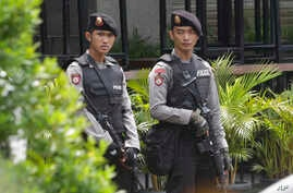 Armed police stand outside the Starbucks cafe where an attack occurred on Thursday, in Jakarta, Indonesia, Jan. 15, 2016.