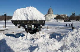 A loader piles a full bucket of snow in front of the U.S. Capitol Building in Washington, D.C., Jan. 24, 2016.