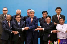 U.S. Secretary of State John Kerry, foreground third left, poses for a group picture with foreign ministers before commencing the 4th East Asia Summit (EAS) Foreign Ministers' Meeting in Naypyitaw, Myanmar, Sunday, Aug. 10, 2014.