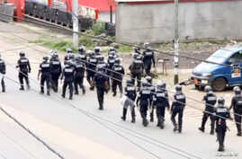 A still image taken from video shows riot police walk along a street in the English-speaking city of Buea, Cameroon Oct. 1, 2017.