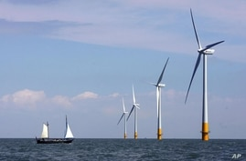 FILE - A boat sails towards a wind farm off the coast of Whitstable, on the coast of southeastern England, July 11, 2006. Britain has invested heavily in renewable energy before reaching Tuesday's first coal-free day milestone.