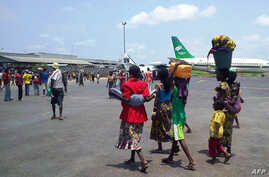 Women and children walk with on the tarmac of Bangui's international airport, Aug. 28, 2013.