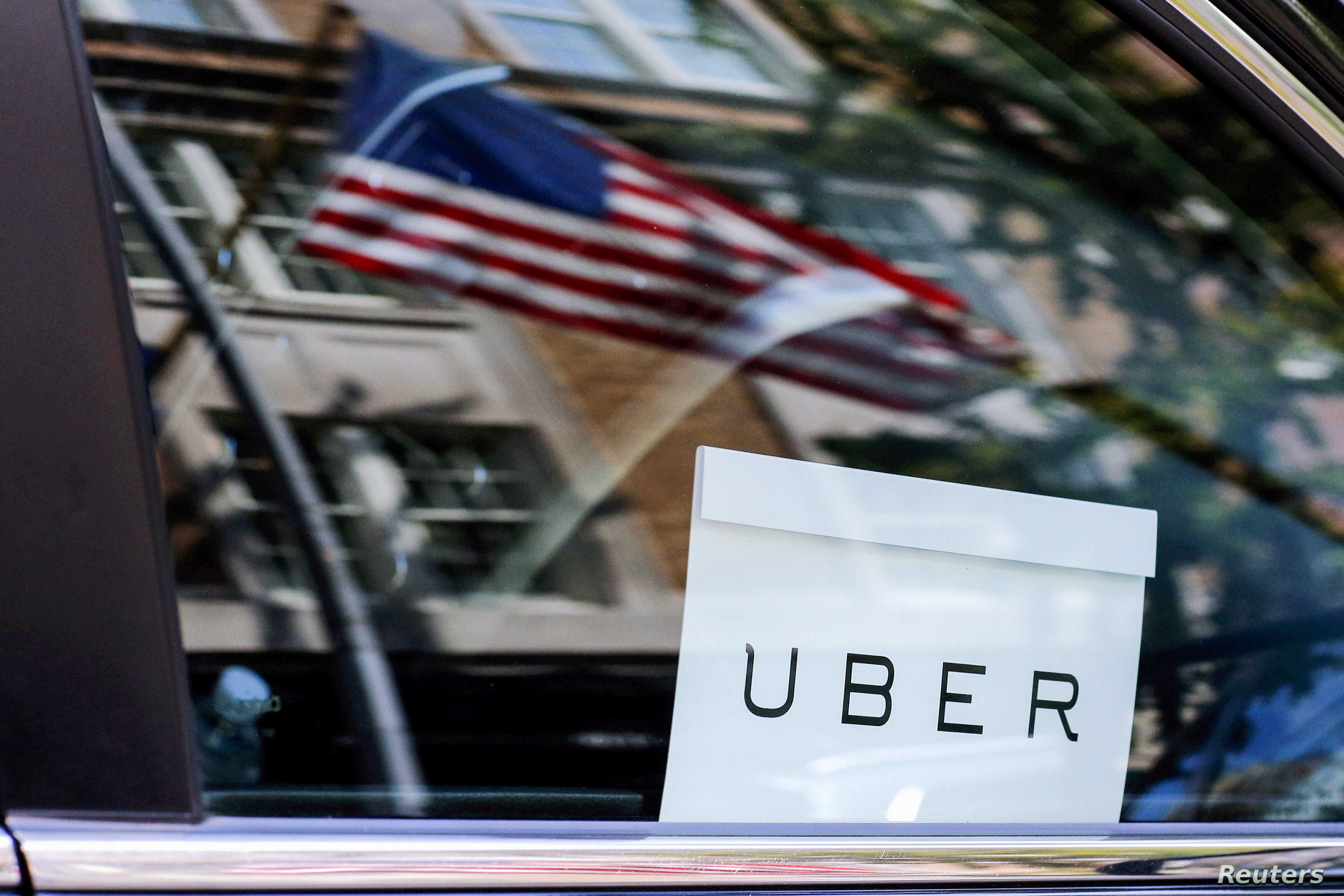 FILE - An Uber sign is seen in a car in New York, NY, U.S.