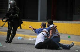 A father challenges a security forces member and prevents him from detaining his son during clashes with anti-government protesters who were trying to march to the Supreme Court, in Caracas, Venezuela, July 6, 2017.