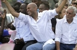 Haiti's presidential candidate Michel Martelly, center, accompanied by fellow candidate Charles-Henri Baker, right, and musician Wyclef Jean ride atop a vehicle through Port-au-Prince to demonstrate against the general elections in Haiti, Sunday, Nov