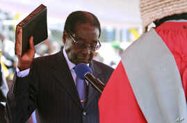 Zimbabwean President Robert Mugabe holds the bible during his inauguration in Harare, August 22, 2013.