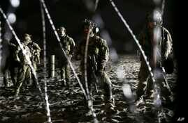 U.S. Border Patrol agents stand on the U.S. side of the border, seen through the concertina wire where the border meets the Pacific Ocean, Thursday, Nov. 15, 2018, from Tijuana, Mexico.