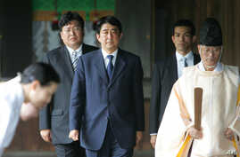 ** FILE ** Shinzo Abe, center, deputy secretary general of Japan's ruling Liberal Democratic Party (LDP), is led by a Shinto priest during his visit to the Yasukuni shrine where Japan's war dead including high-ranking war criminals have been enshrine