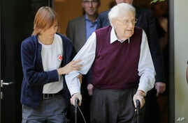 FILE - With the help of a Red Cross worker, former SS guard Oskar Groening, right, leaves the court after the verdict of his trial in Lueneburg, Germany, July 15, 2015.