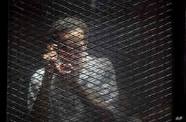 FILE - Egyptian photojournalist Mahmoud Abu Zeid, known by his nickname Shawkan, gestures in a soundproof glass cage inside a makeshift courtroom in Tora prison in Cairo, Egypt, July 28, 2018.