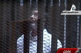 In this image taken from Egypt State TV,  Mohammed Morsi stands inside a glass-encased metal cage in a courtroom in Cairo, Jan. 28. 2014.