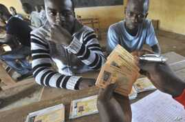Men wait to retreive their identity cards as well as their electors cards for the presidential elections iin Bouake, Oct 27, 2010
