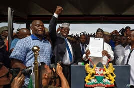"FILE - opposition politician Miguna Miguna, center, raises his fist as a gesture to the crowd as he stands next to opposition leader Raila Odinga, center-right, and politician James Orengo, far right, as Odinga holds an oath during a mock ""swearing-i"