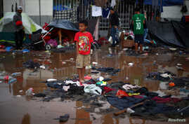 A migrant boy, part of a caravan of thousands from Central America trying to reach the United States, stands in a temporary shelter after heavy rainfall in Tijuana, Mexico, Nov. 29, 2018.
