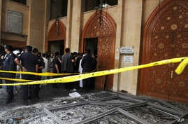 Security forces and officials gather at a Shiite mosque after a deadly blast claimed by the Islamic State group that struck worshipers attending Friday prayers in Kuwait City, June 26, 2015.