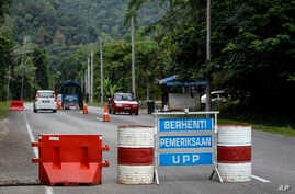 A check point is seen at the entry point to Malaysia - Thailand border in Wang Kelian, Malaysia on Sunday, May 24, 2015. Malaysian authorities said Sunday that they have discovered graves in more than a dozen abandoned camps used by human traffickers