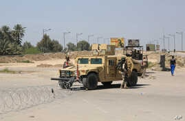 Iraqi soldiers stand guard at the site near a suicide attack that targeted a checkpoint manned by Iraqi troops, in Baghdad, Iraq, April 4, 2016.