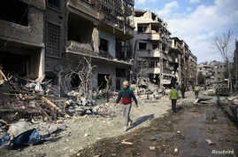 People walk through the damage, after an air raid in the besieged town of Douma, Eastern Ghouta, Damascus, Syria, Feb. 23, 2018.