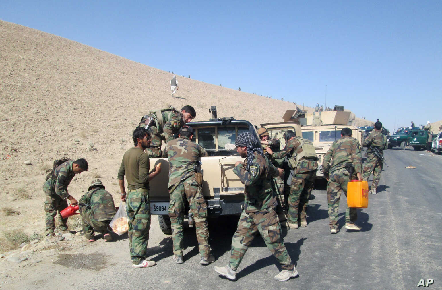 Members of Afghan security forces and volunteer militias break on their way to Kunduz, Afghanistan, to fight against Taliban militants, Oct. 1, 2015.
