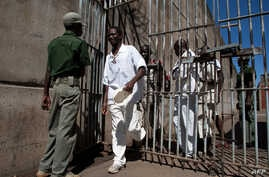 Prison Inmates walk past a prison guard at the Chikurubi Maximum security prison in Harare, Zimbabwe, May 20, 2015 during a tour by a parliamentary committee to assess the state of the nation's prisons where inmates widely complained of food shortage