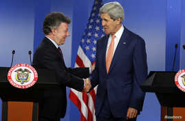 U.S. Secretary of State John Kerry (R) and Colombia's President Juan Manuel Santos shake hands as they address a joint news conference after their meeting at the presidential palace in Bogota, Dec. 12, 2014.