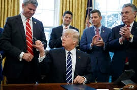 FILE - President Donald Trump hands a pen to Congressman Bill Huizenga, R-Michigan, after signing House Joint Resolution 41 in the White House in Washington, Feb. 14, 2017.