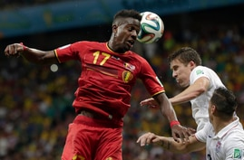 Belgium's Divock Origi heads the ball over United States' Matt Besler and Geoff Cameron, right, during the World Cup round of 16 soccer match between Belgium and the USA at the Arena Fonte Nova in Salvador, Brazil, July 1, 2014.
