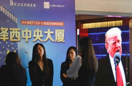 A projector screen shows a footage of U.S. President Donald Trump as workers wait for investors at a reception desk during an event promoting EB-5 investment in a Kushner Companies development at a hotel in Shanghai, China, May 7, 2017.