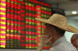 An investor looks at an electric board showing stock information at a brokerage house in Haikou, Hainan province, China, Aug. 11, 2015.