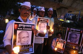 FILE - Supporters of India's Aam Aadmi Party (AAP), or Common Man's Party, hold portraits of scholar Malleshappa M. Kalburgi during a candlelight vigil Tuesday in Bangalore to protest his weekend killing.
