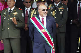 Suriname President Desire Delano Bouterse observes a military parade, after being sworn in for his second term, in Paramaribo, Suriname. The high court in Suriname says the trial of Bouterse in the killings of 15 political opponents in 1982 must resu